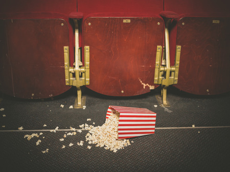 spilled: A bucket of spilled popcorn on the floor of a movie theater