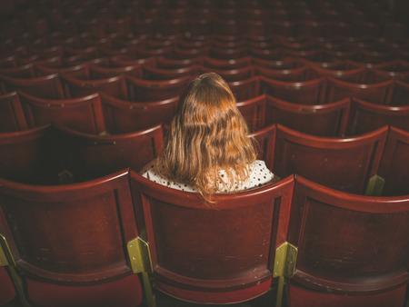 강당에서 혼자 앉아 젊은 여자의 후면보기 샷