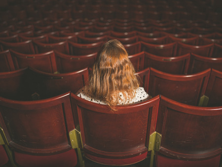 girl alone: Rear view shot of a young woman sitting alone in an auditorium
