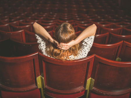 Rear view shot of a young woman sitting alone in an auditorium