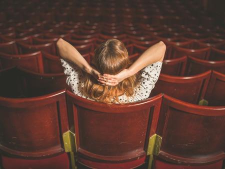 solos: Vista posterior disparo de una mujer joven sentada sola en un auditorio