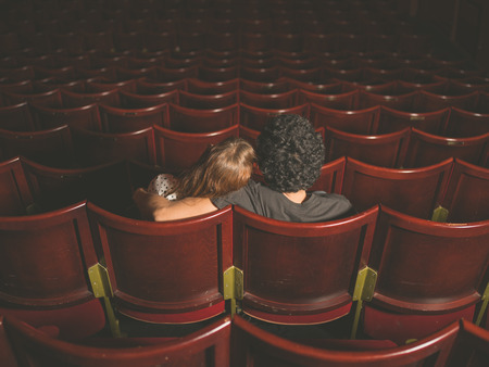 movie: Rear view shot of a young couple sitting in a movie theater