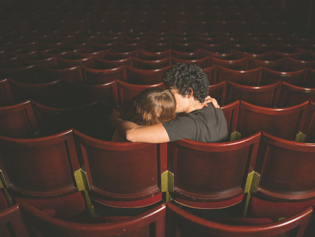 love seat: Rear view shot of a young couple sitting in a movie theater and kissing