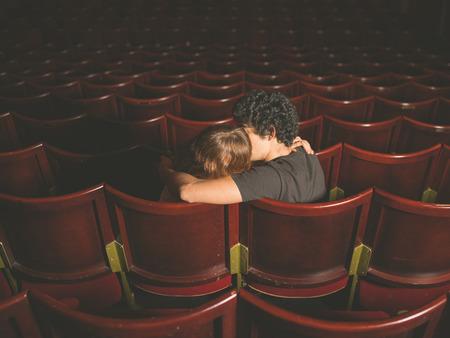 haciendo el amor: Vista posterior disparo de una pareja de jóvenes sentados en una sala de cine y besos