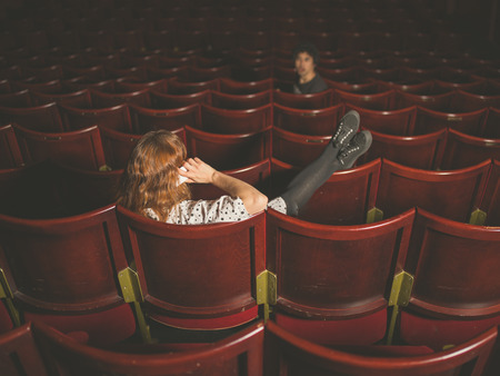 annoying: A young woman is talking on her phone in an auditorium and is annoying a man a few rows in front of her Stock Photo