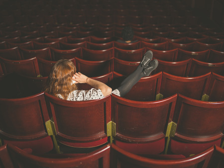 disrespect: A young woman is talking on her phone in an auditorium
