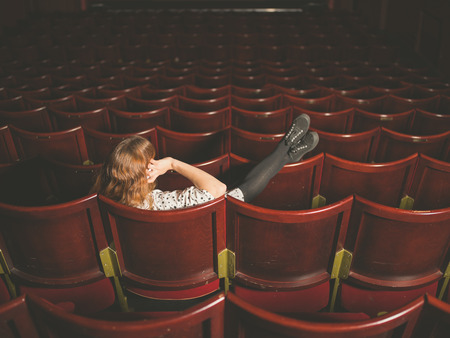 A young woman is talking on her phone in an auditorium photo