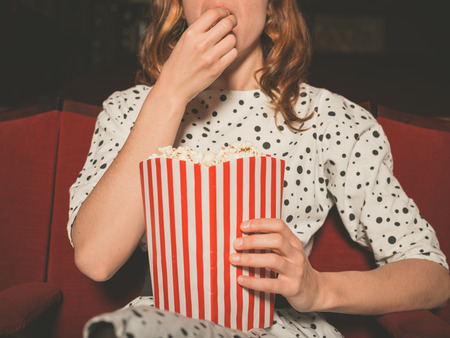 A young woman is watching a movie and is eating popcorn at the cinema