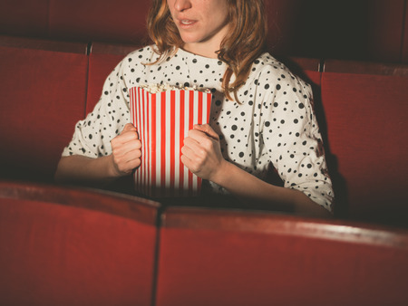 suspense: A young woman is watching a suspense movie at the cinema and is clutching her popcorn Stock Photo
