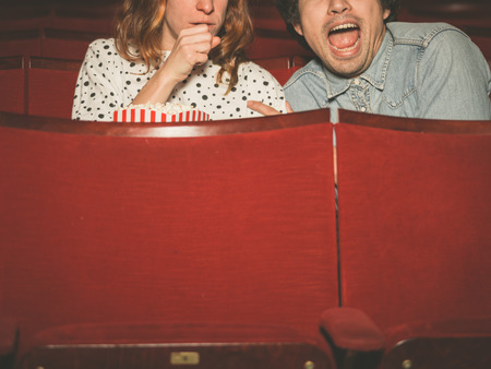 A young couple is watching a scary film in a movie theater