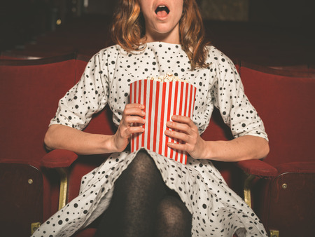 palomitas de maiz: Una mujer joven está sentado en la primera fila en una sala de cine y está viendo una película emocionante mientras come palomitas