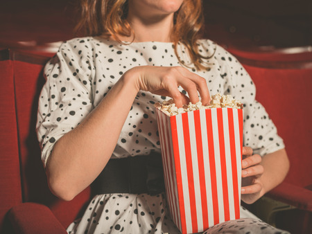 at the theater: Closeup on a young woman eating popcorn in a movie theater