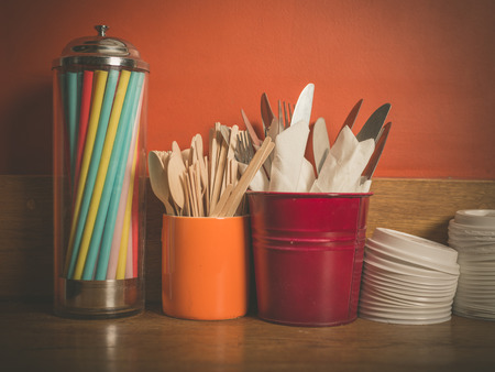 lids: A selection of cutlery, colorful straws and plastic lids for disposable cups on a wooden table