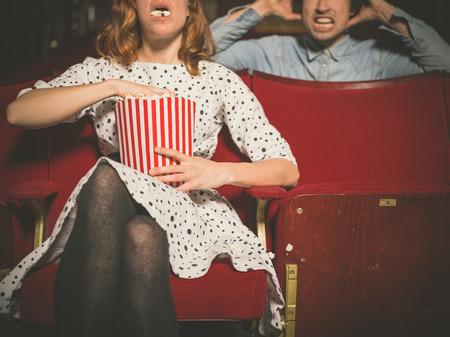 molesto: Una mujer joven est� comiendo palomitas de ma�z en voz alta en una sala de cine y es molesto el hombre sentado detr�s de ella