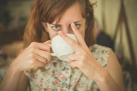 finger food: A young woman is drinking coffee and is displaying an obscene gesture with her fingers