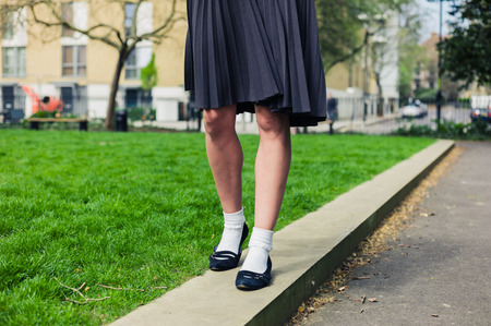 uniform green shoe: A young woman wearing a skirt is walking in a park by the green grass Stock Photo