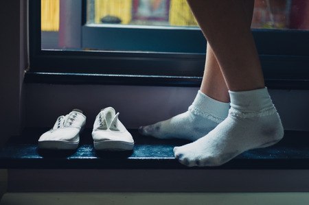 sock: The feet of a young woman wearing white socks and standing by a door leading to a balcony