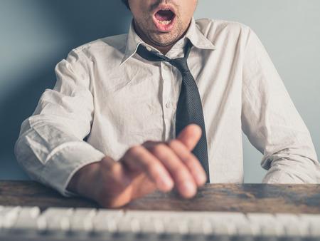 若いビジネスマンは 1 つの手でコンピューターに入力されています。もう一方の手はテーブルの下で、彼は本当に興奮しています。 写真素材