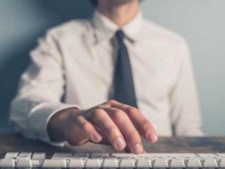 formal clothes: A young businessman is typing on a keyboard