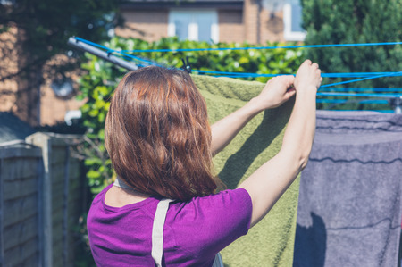 A young woman is hanging her laundry on a clothes line in the garden on a sunny day photo