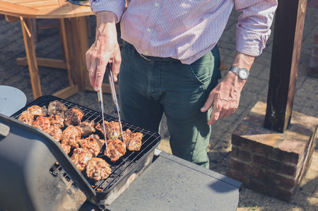 A senior man is grilling pieces of chicken on a barbecue in a garden on a sunny day Standard-Bild
