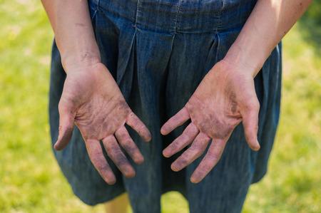 manos sucias: Una mujer joven est� mostrando sus manos sucias cubiertas de suciedad de la jardiner�a