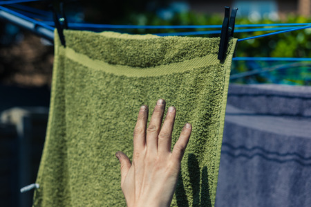 muck: A dirty hand covered in muck is about to touch some clean laundry hanging on a clothes line
