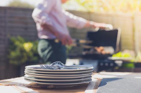 バーベキューに参加する男と庭の外テーブルでプレートのスタック 写真素材