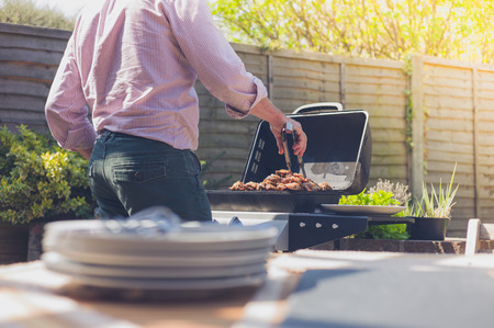Stack of plates on a table outside in a garden with a man attending to a barbecue