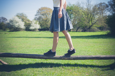 balance: A young woman is walking in the forest and is balancing on a wooden beam Stock Photo