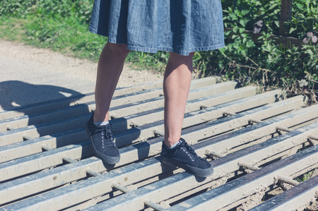 cattle grid: A young woman is walking on a cattle grid Stock Photo