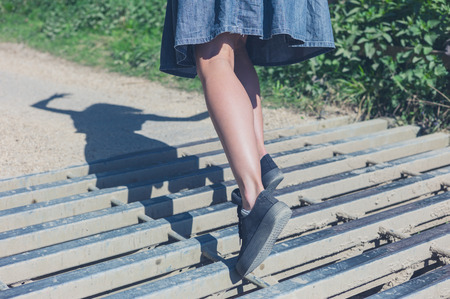 tripping: A young woman is tripping on a cattle grid in the countryside