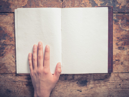 A male hand and a big notepad on a wooden table