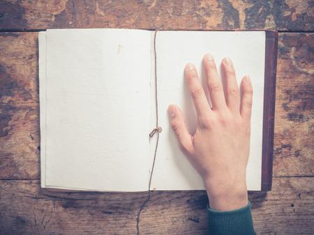 persona escribiendo: Una mano masculina y un gran bloc de notas en una mesa de madera Foto de archivo