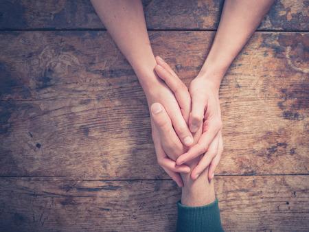 casamento: Feche acima em um homem e uma mulher segurando as mãos em uma mesa de madeira Banco de Imagens