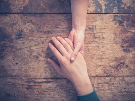 木製のテーブルで手を繋いでいる男女にクローズ アップ