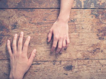 casamento: Um macho e uma fêmea da mão em uma mesa de madeira Banco de Imagens