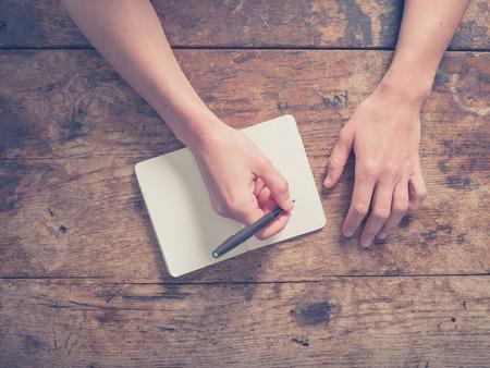 persona escribiendo: Cierre en las manos de una mujer joven como ella está escribiendo en un pequeño bloc de notas en una mesa de madera