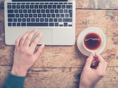 彼はラップトップを使用して木製のテーブルでコーヒーのカップを持っている、男の手のクローズ アップ