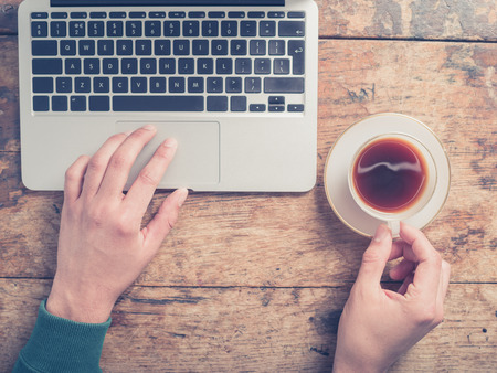 Close up on the hands of a man as he is using a laptop and having a cup of coffee at a wooden table Archivio Fotografico