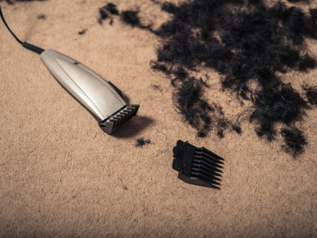 hair clippers: Some hair clippers on the floor with piles of hair around them