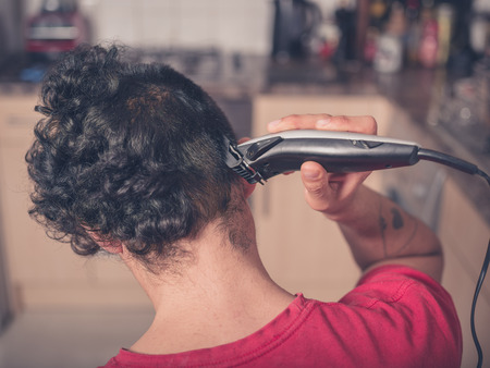 hair clippers: A young man is using hair clippers to give himself a haircut in his kitchen
