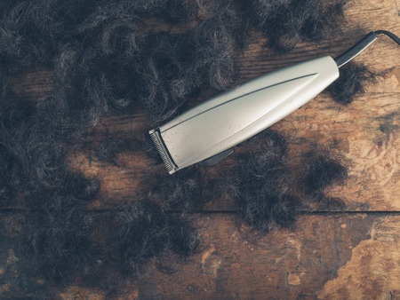 hair clippers: Hair clippers on a wooden surface surrounded by piles of cut hair Stock Photo