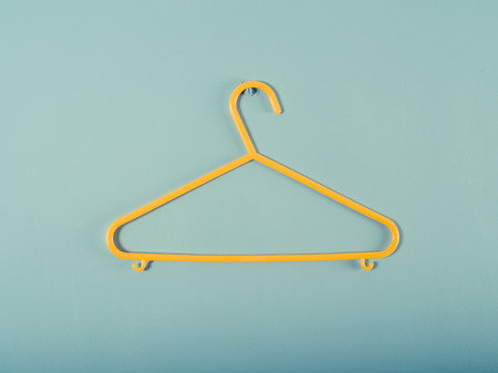 A yellow plastic hanger is hanging on a blue wall photo