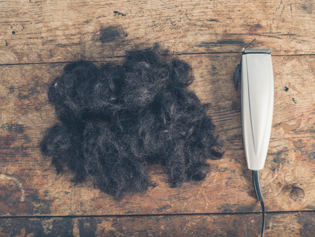 hair clippers: A large pile of cut hair and some clippers on a wooden table
