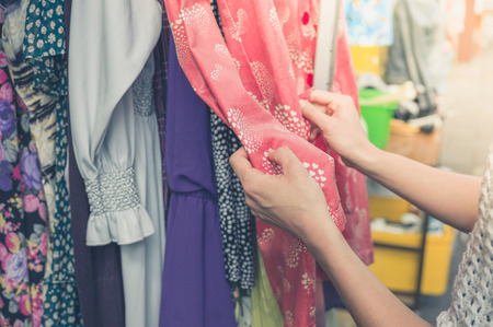 A young woman is browsing through clothing at a street market