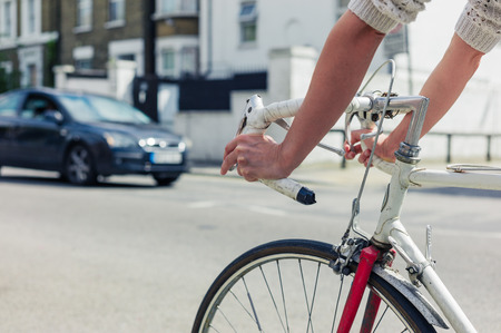road cycling: A young woman is cycling on the road in a city on a sunny day Stock Photo