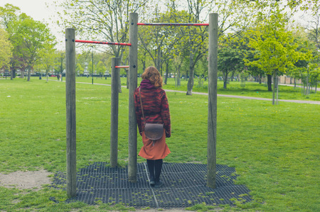 pull up: A young woman is standing in a park by some pull up bars