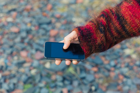 geolocation: A young woman is using her smartphone outside with gravel and rubble on the ground