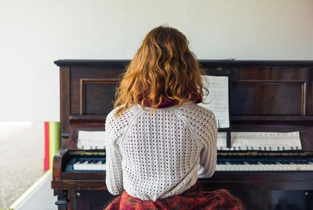 젊은 여자가 피아노를 연주한다